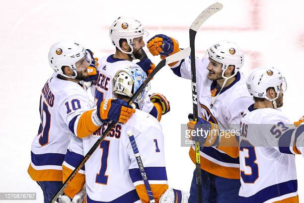 Thomas Greiss, Derick Brassard and Mathew Barzal of the New York Islanders celebrate their 4-0 victory against the Philadelphia Flyers in Game Seven...