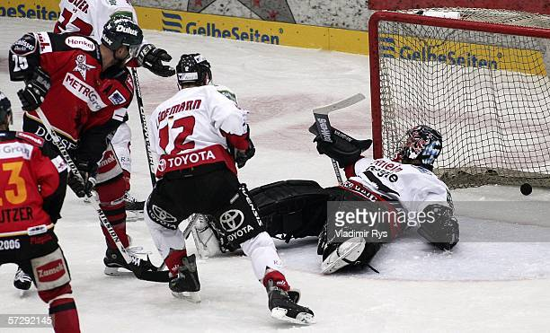Thomas Greiss of Cologne Haie receives a goal from Craig Johnson of Metro Stars during the DEL Play Off Semi Final fifth match between DEG Metro...