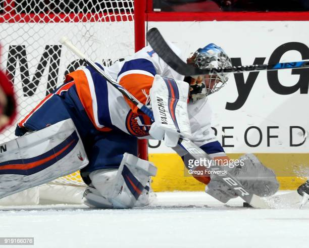 Thomas Greiss of the New York Islanders dives on a loose puck during an NHL game against the Carolina Hurricanes on February 16 2018 at PNC Arena in...