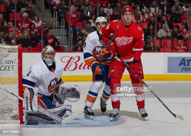 Thomas Greiss of the New York Islanders follows the play as teammate Brandon Davidson defends against Anthony Mantha of the Detroit Red Wings during...