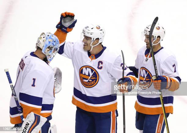 Thomas Greiss of the New York Islanders is congratulated by teammates Anders Lee and Jordan Eberle after the 21 win over the New York Rangers during...