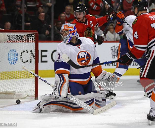 Thomas Greiss of the New York Islanders looks over his shoulder at the puck after the Chicago Blackhawks scored the gametying score in the third...