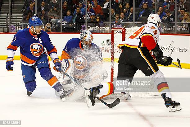 Thomas Greiss of the New York Islanders makes a save against Micheal Ferland of the Calgary Flames as Travis Hamonic looks on at the Barclays Center...