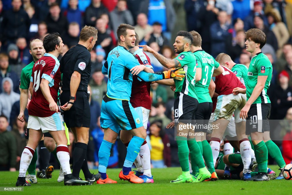 Thomas Heaton of Burnley (CL) and Nathan Arnold of Lincoln City (CR) argue during The Emirates FA Cup Fifth Round match between Burnley and Lincoln City at Turf Moor on February 18, 2017 in Burnley, England.