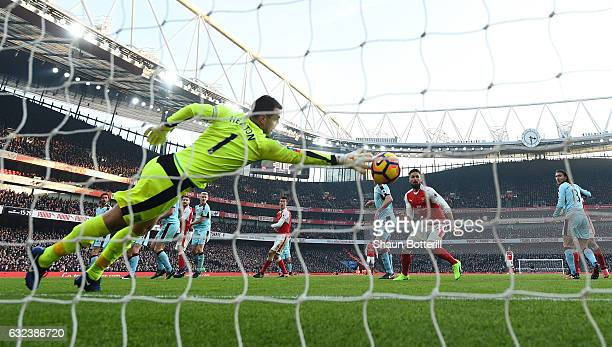 Thomas Heaton of Burnley dives in vain as Shkodran Mustafi of Arsenal heads to score the opening goal during the Premier League match between Arsenal...