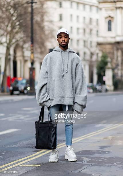 Thomas Hervey wearing an oversized grey hoody white flex cap black hand bag skinny denim jeans platform shoes during London Fashion Week Men's...
