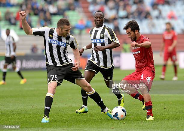 Thomas Heurtaux and Emanuel Badu of Udinese compete with Maurizio Pinilla of Cagliari during the Serie A match between Udinese Calcio and Cagliari...