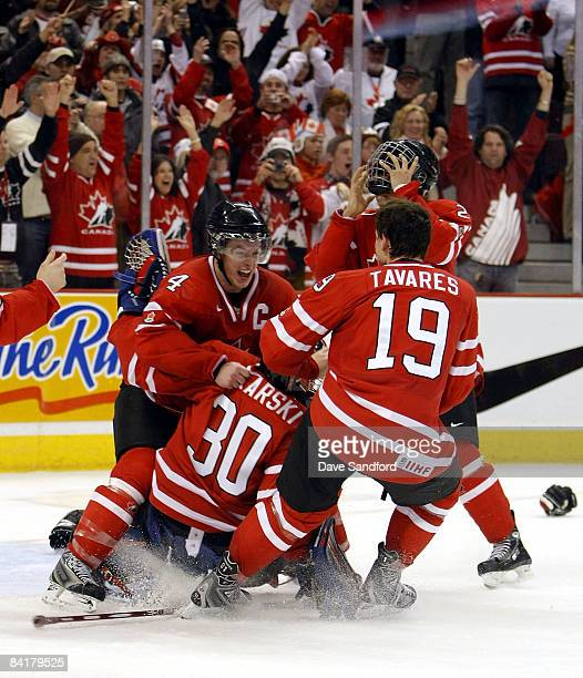 Thomas Hickey and John Tavares both of Team Canada celebrate with teammate Dustin Tokarski as the horn sounds to defeat Team Sweden during the 2009...
