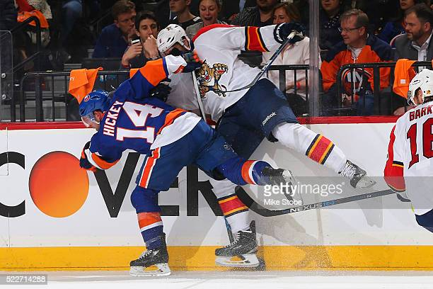 Thomas Hickey of the New York Islanders and Alex Petrovic of the Florida Panthers get tangled up against the boards in Game Four of the Eastern...