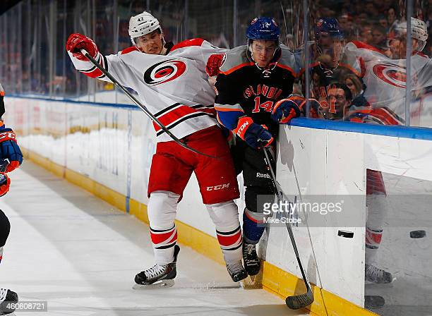 Thomas Hickey of the New York Islanders and Brett Sutter of the Carolina Hurricanes pursue the puck at Nassau Veterans Memorial Coliseum on January...