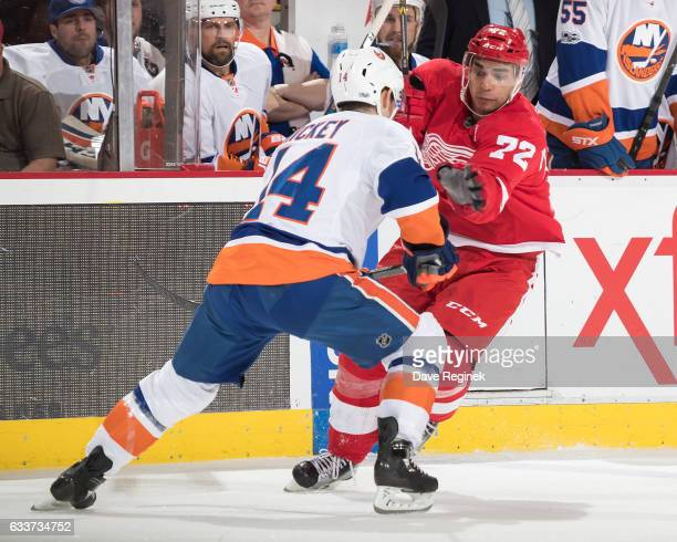 Thomas Hickey of the New York Islanders battles for position with Andreas Athanasiou of the Detroit Red Wings during an NHL game at Joe Louis Arena...