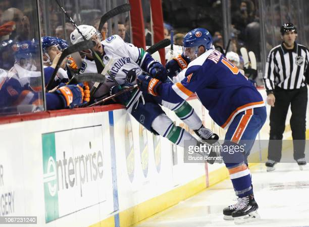 Thomas Hickey of the New York Islanders checks Brendan Leipsic of the Vancouver Canucks during the third period at the Barclays Center on November 13...