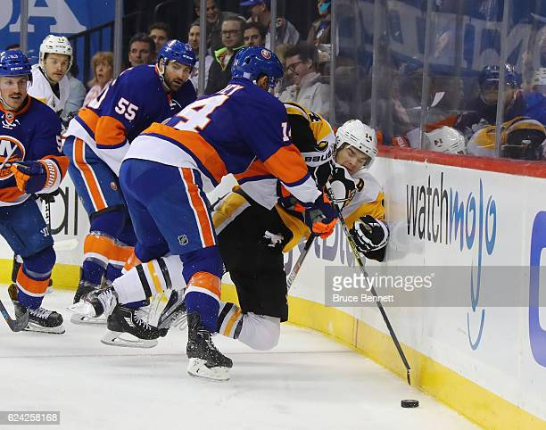 Thomas Hickey of the New York Islanders hits Chris Kunitz of the Pittsburgh Penguins into the boards during the first period at the Barclays Center...
