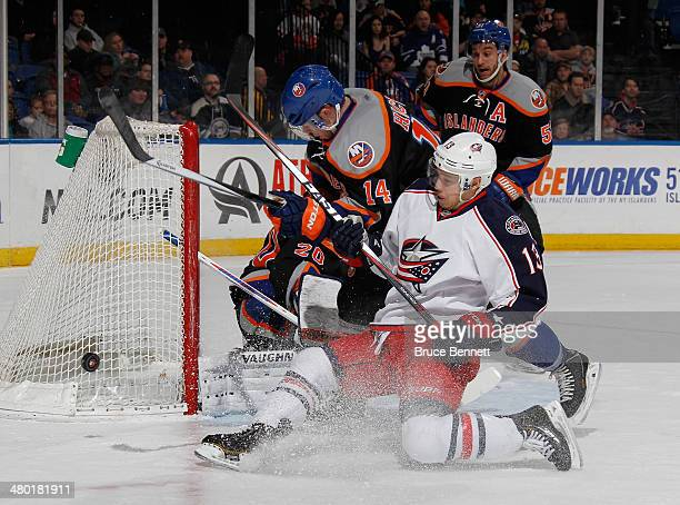 Thomas Hickey of the New York Islanders holds up Cam Atkinson of the Columbus Blue Jackets as he takes the first period shot at the Nassau Veterans...
