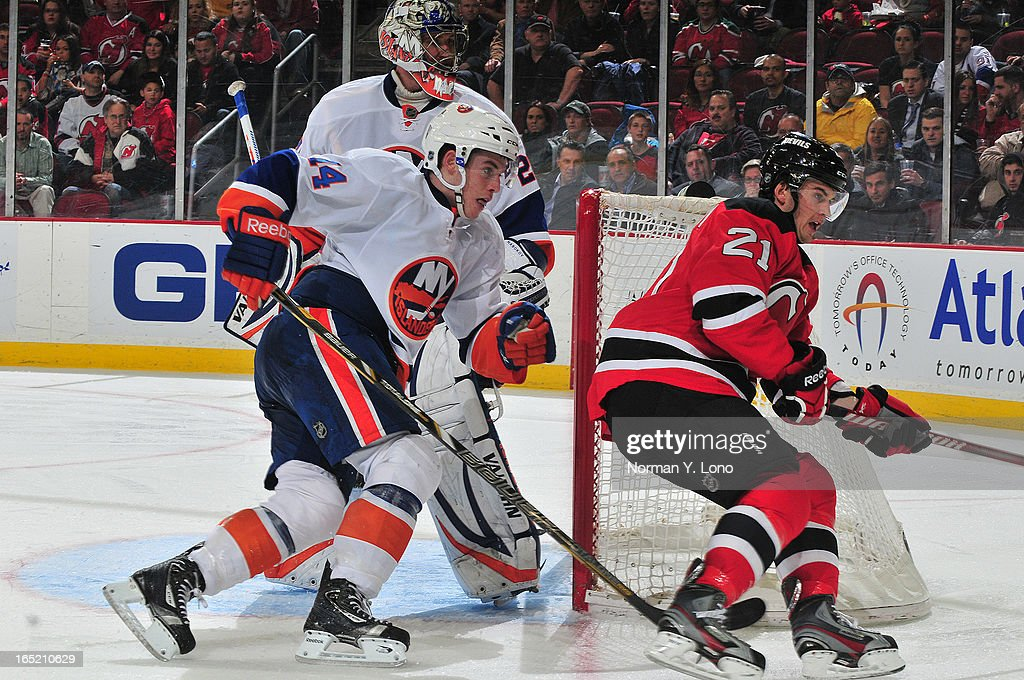 Thomas Hickey #14 of the New York Islanders keeps his eyes on Andrei Loktionov # #21 of the New Jersey Devils at the Prudential Center on April 1, 2013 in Newark, New Jersey. Islanders win 3-1 over the Devils.