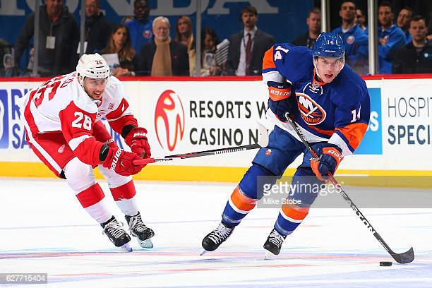 Thomas Hickey of the New York Islanders plays the puck against Mike Green of the Detroit Red Wings at the Barclays Center on December 4 2016 in...
