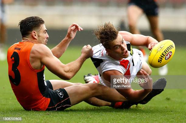 Thomas Highmore of the Saints is tackled by Stephen Coniglio of the Giants during the round one AFL match between the GWS Giants and the St Kilda...