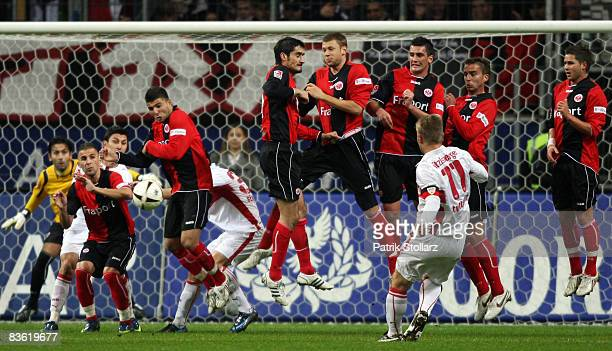 Thomas Hitzlsperger of Stuttgart takes a freekick as players of Frankfurt jump in the wall during the Bundesliga match between Eintracht Frankfurt...
