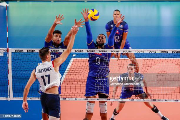 Thomas Jaeschke of USA spikes the ball against Barthelemy Chinenyeze and Earvin Ngapeth of France during the friendly game between France and USA at...