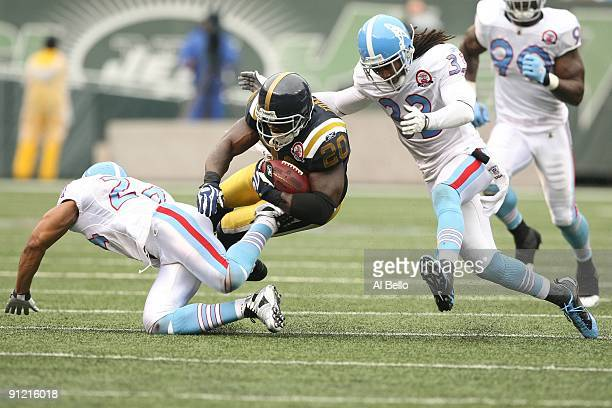 Thomas Jones of The New York Jets is chased by Chris Hope and Michael Griffin of The Tennessee Titans during their game on September 27 2009 at...