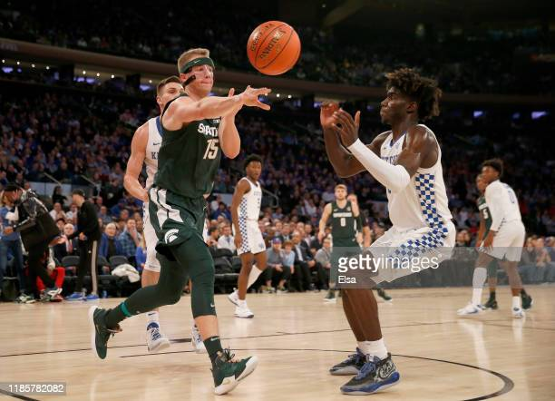 Thomas Kithier of the Michigan State Spartans passes the ball as Kahlil Whitney of the Kentucky Wildcats defends during the State Farm Champions...
