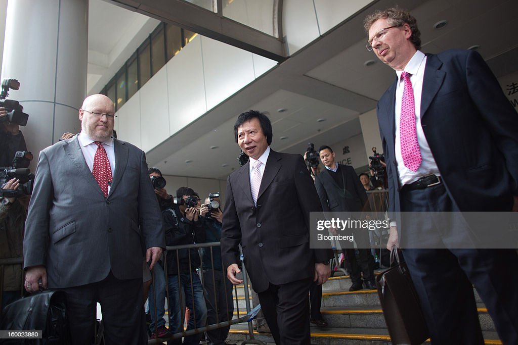 Thomas Kwok, co-chairman of Sun Hung Kai Properties Ltd., center, exits the Eastern Magistrates' Court in Hong Kong, China, on Friday, Jan. 25, 2013. The prosecution's bribery case against Sun Hung Kai's billionaire co-chairmen Thomas and Raymond Kwok and Hong Kong's former No. 2 official Rafael Hui will be ready by March, a court was told. Photographer: Lam Yik Fei/Bloomberg via Getty Images