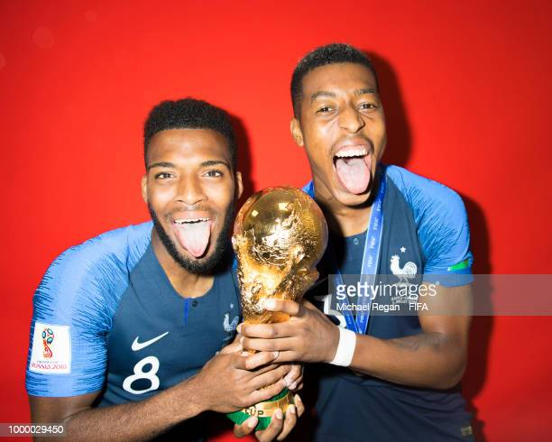 Thomas Lemar and Presnel Kimpembe of France pose with the Champions World Cup trophy after the 2018 FIFA World Cup Russia Final between France and...