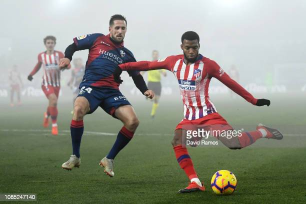 Thomas Lemar of Atletico Madrid crosses the ball under pressure from Jorge Miramon of SD Huesca during the La Liga match between SD Huesca and Club...