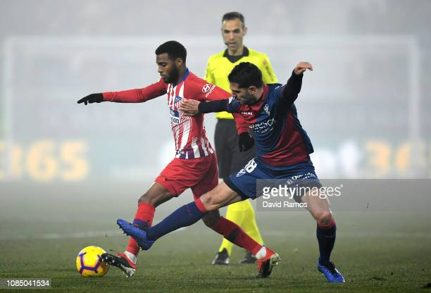 Thomas Lemar of Atletico Madrid is challenged by Pablo Insua of SD Huesca during the La Liga match between SD Huesca and Club Atletico de Madrid at...
