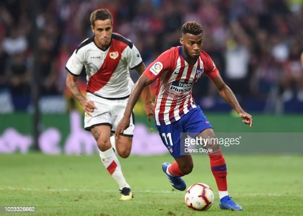 Thomas Lemar of Club Atletico de Madrid gets away from Oscar Trejo of Rayo Vallecano de Madrid during the La Liga match between Club Atletico de...