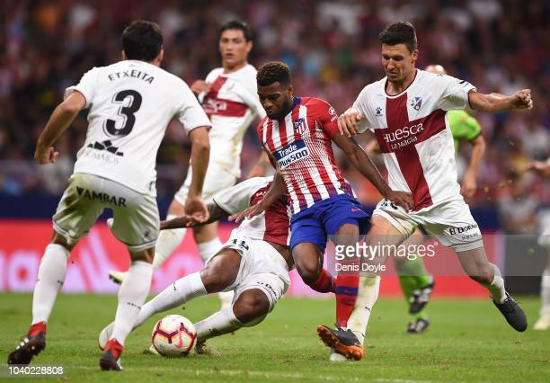 Thomas Lemar of Club Atletico de Madrid is tackled by Damian Marcelo Musto and Ruben Semedo of SD Huesca of SD Huescaduring the La Liga match...