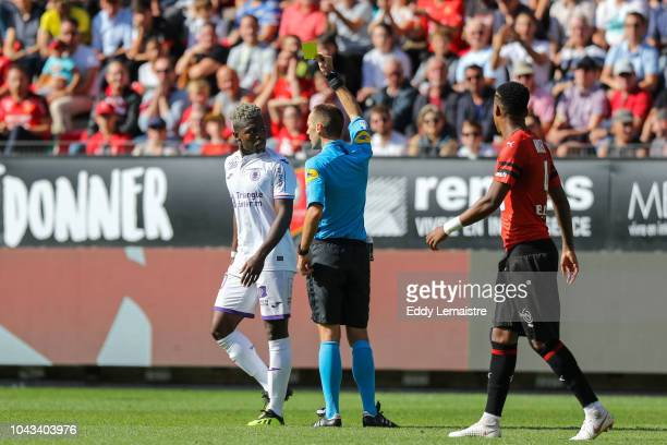 Thomas Leonard referee give a yellow card at Aaron Leya Iseka of Toulouse during the Ligue 1 match between Rennes and Toulouse at Roazhon Park on...