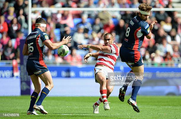 Thomas Leuluai of Wigan kicks past Mark Flanagan and Josh Perry of St Helens during the Carnegie Challenge Cup Quarter Final match between Wigan and...