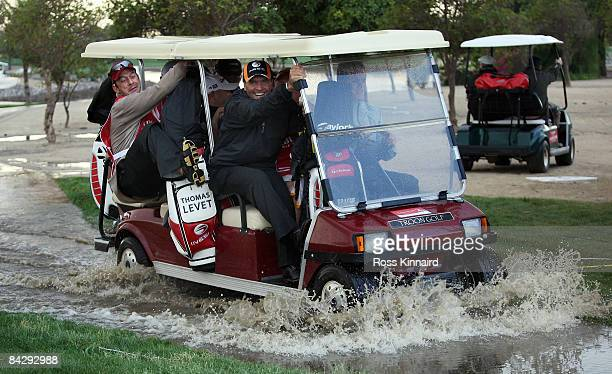 Thomas Levet of France makes his way back to the club house in a buggy as rain halts play during the first round the Abu Dhabi Golf Championship at...