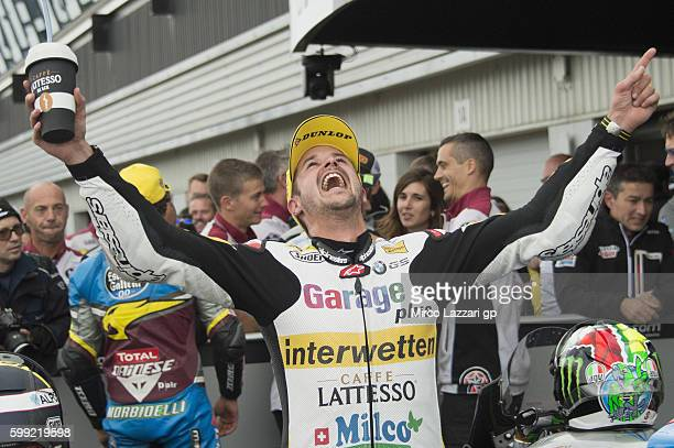Thomas Luthi of Switzerland and Garage Plus Interwetten celebrates the victory under the podium at the end of the Moto2 race during the MotoGp Of...