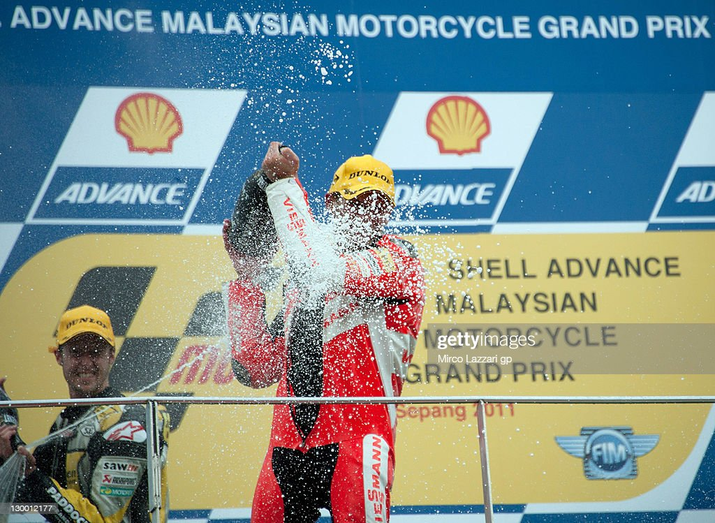 Thomas Luthi of Switzerland and Interwetten Paddock and Stefan Bradl of Germany and Viessmann Kiefer Racing celebrate and spray champagne on the podium at the end of the Moto2 race of MotoGP of Malaysia at Sepang Circuit on October 23, 2011 in Kuala Lumpur, Malaysia.