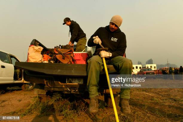 Thomas McClure a firefighter with a type II hand crew from Mission Valley Montana sharpens his hand tools before he and his crew head out onto the...
