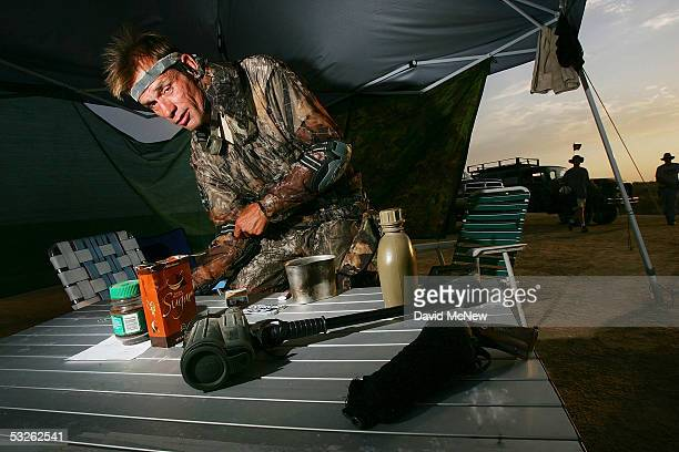 Thomas McMullen prepares his gear, including camouflage, spotting scope and a pistol , for a covert approach in the controversial nightly patrol by...