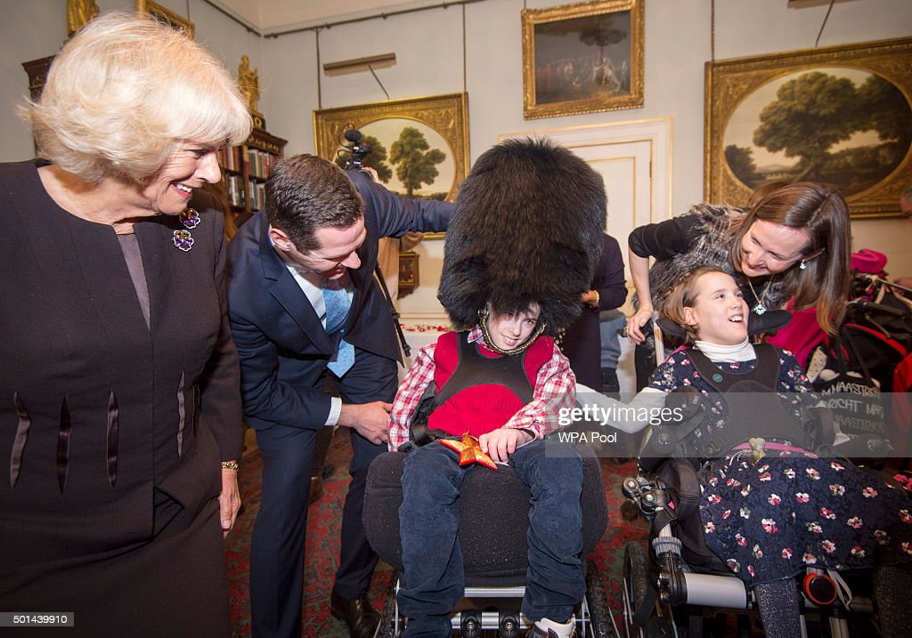 Thomas Melville-Ross 12 trys on a Guards bearskin hat with his sister Alice 12 with Camilla, Duchess of Cornwall, patron of the Helen & Douglas House and The London Taxidrivers' Fund as she invites underprivileged children from both charities to decorate the Christmas tree and join the Duchess for Christmas lunch at Clarence House on December 15, 2015 in London, England.