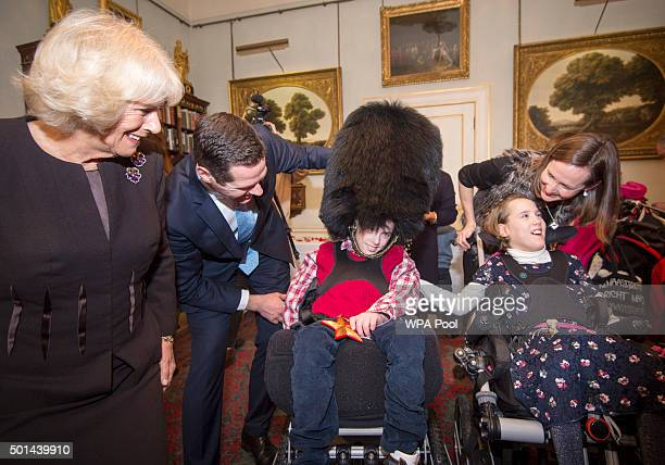 Thomas MelvilleRoss 12 trys on a Guards bearskin hat with his sister Alice 12 with Camilla Duchess of Cornwall patron of the Helen Douglas House and...
