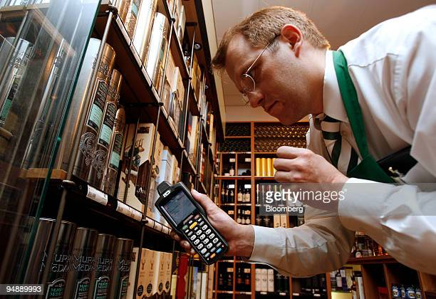 Thomas Meyer uses an electronic device to check whisky inventory at a Metro AGowned Kaufhof department store at Alexanderplatz in Berlin Germany on...
