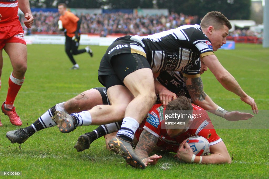Thomas Minns of Hull KR scores a try as Jamie Shaul and Jake Connor of Hull FC tackle him during the BetFred Super League match between Hull KR and Hull FC at KCOM Craven Park on March 30, 2018 in Hull, England.