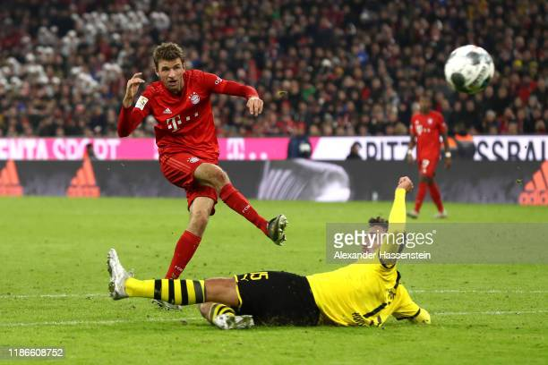 Thomas Müller of FC Bayern Muenchen battles for the ball with Mats Hummels of Dortmund during the Bundesliga match between FC Bayern Muenchen and...