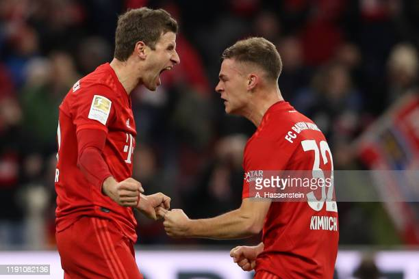 Thomas Müller of FC Bayern Muenchen celebrates scoring the first team goal with his team mate Joshua Kimmich during the Bundesliga match between FC...