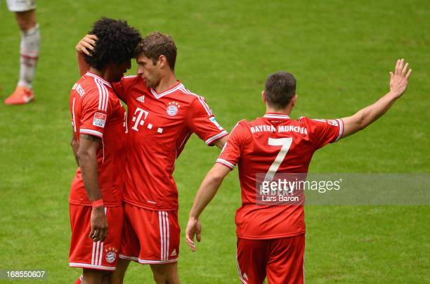 Thomas Müller of Germany celebrates with his teammate Dante after scoring the opening goal during the Bundesliga match between FC Bayern Muenchen and...