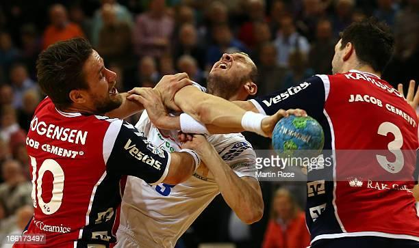 Thomas Mogensen and Tobias Karlsson of Flensburg are challenged by Pascal Hens of Hamburg during the DKB Handball Bundesliga match between SG...