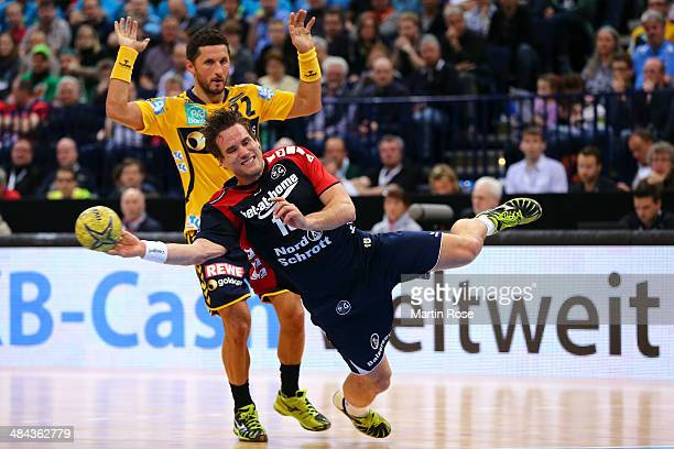 Thomas Mogensen of Flensburg challenges for the ball with Alexander Petersson of Rhein Neckar Loewen during the DHB Pokal handball semi final match...