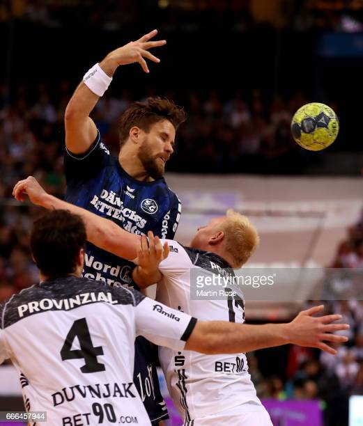 Thomas Mogensen of Flensburg challenges Patrick Wiencek of Kiel for the ball during the Rewe Final Four final match between SG FlensburgHandewitt and...