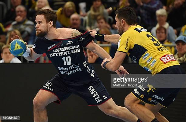 Thomas Mogensen of SG Flensburg Handewitt is challenged by Alexander Petersson of RheinNeckar Loewen during the DKB HBL Bundesliga match between...