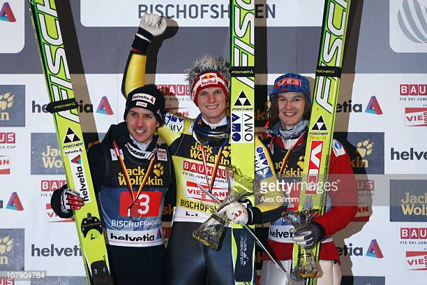 Thomas Morgenstern of Austria celebrates winning the 59th Four Hills ski jumping tournament with second placed Simon Ammann of Switzerland and third...
